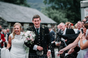 Bride and groom walking through confetti at Llyn Gwynant Campsite