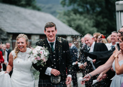 Bride and groom walking through confetti at Llyn Gwynant Campsite