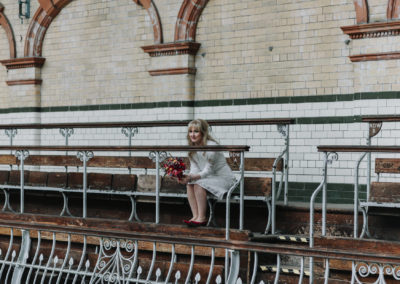Portrait of smiling bride holding bouquet while overlooking the pool at Victoria Baths in Manchester