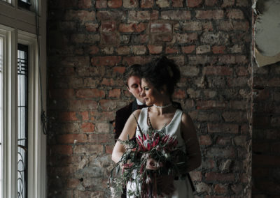 photograph of bride and groom standing by decorative window at Victoria Baths in Manchester