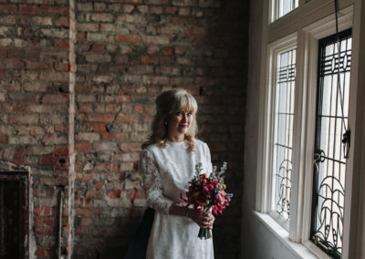 portrait of bride holding bouquet at Victoria Baths in Manchester