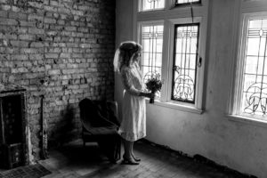 black and white portrait of bride holding bouquet at Victoria Baths in Manchester