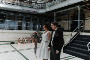 bride and groom walk past light up love sign at victoria baths in Manchester