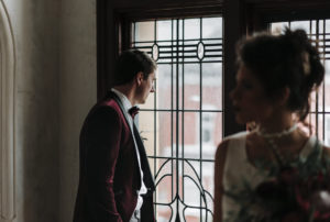 Groom in maroon suede jacket peering out of decorative window in Victoria Baths in Manchester