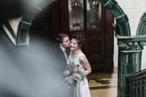 groom kissing brides cheek in archway at Victoria Baths in Manchester