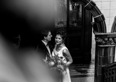 black and white photograph of bride and groom standing in archway at Victoria Baths in Manchester