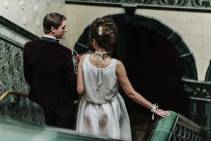Bride and groom descending down green tiled staircase at Victoria Baths in Manchester