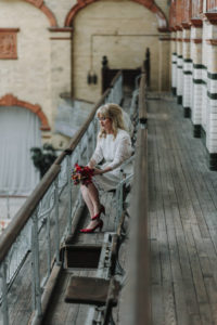 Portrait of bride holding bouquet while overlooking the pool at Victoria Baths in Manchester