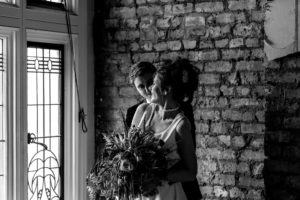 Black and white photograph of a smiling bride and groom standing by decorative window at Victoria Baths in Manchester